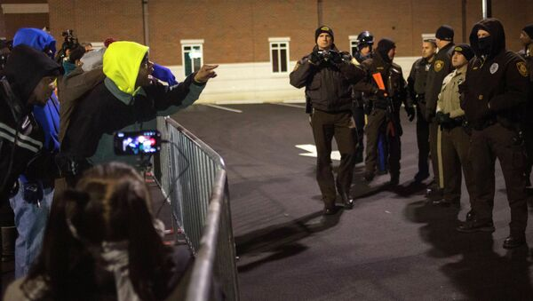 Protesters shout towards police as they demand the criminal indictment of a white police officer who shot dead an unarmed black teenager in August, outside the Ferguson Police Station in Missouri November 20, 2014 - Sputnik International