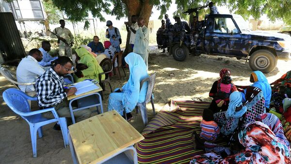 Special Prosecutor for Crimes in Darfur Yasir Ahmed Mohamed (back, in blue shirt with glasses) and his team talk to women during an investigation into allegations of mass rape in the village of Tabit - Sputnik International