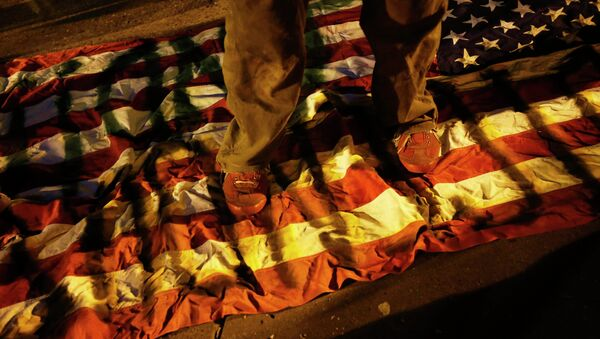 A demonstrator steps on an American flag during a demonstration following the grand jury decision in the Ferguson, Missouri shooting of Michael Brown, in Oakland, California - Sputnik International