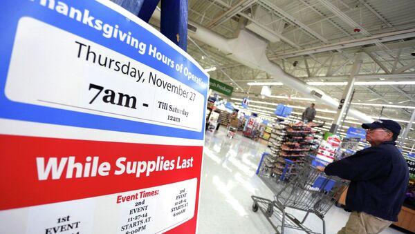 A man walks near a sign at Walmart as the store prepares for Black Friday in Los Angeles, California November 24, 2014 - Sputnik International