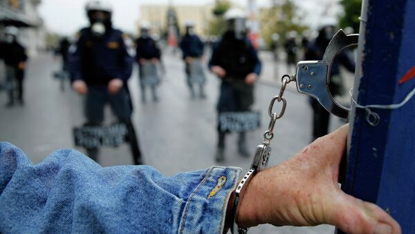 A protester wears handcuffs as he stands in front of riot police following a march during a 24-hour general strike in central Athens November 27, 2014 - Sputnik International