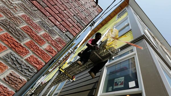 In this Friday, Aug. 17, 2012, file photo, a worker adjusts a scaffold at the site of a new residential construction project in the East Boston neighborhood of Boston - Sputnik International