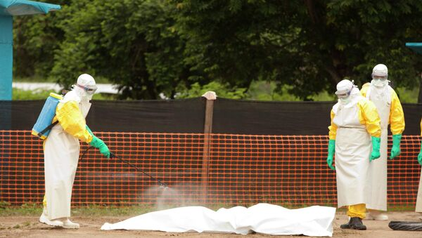 Medical workers are disinfecting the dead body of an Ebola patient. - Sputnik International