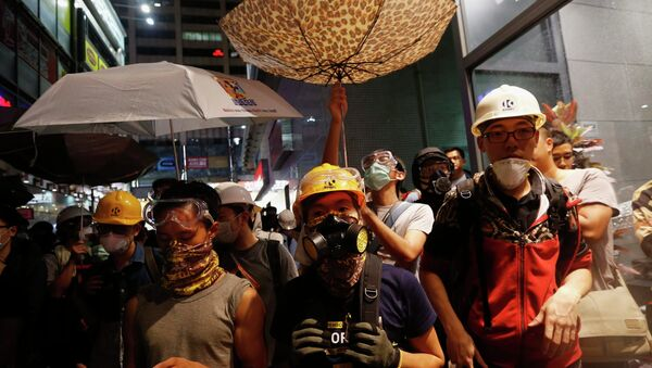 Protesters protect themselves from being sprayed with tear spray during a confrontation with riot police at Mongkok shopping district in Hong Kong - Sputnik International