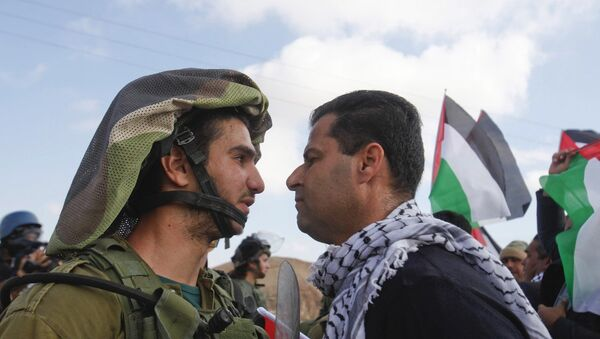 An Israeli soldier argues with a Palestinian protester - Sputnik International