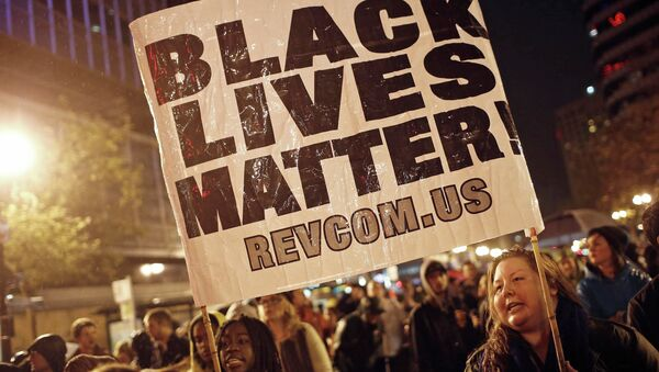 Protesters hold a sign during a march against the New York City grand jury decision to not indict in the death of Eric Garner, in Oakland, California December 3, 2014. - Sputnik International