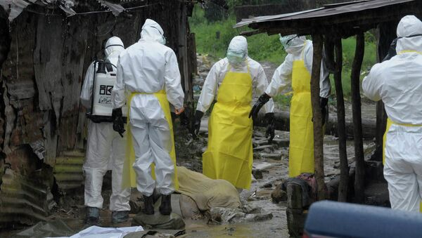 Health workers wearing protective clothing prepare to carry an abandoned dead body presenting with Ebola symptoms - Sputnik International