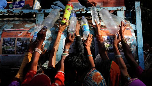 Indian women protesters from the Indian state fill their bottles with drinking water as they participate in a rally in New Delhi, India, Tuesday, Dec. 2, 2014 - Sputnik International