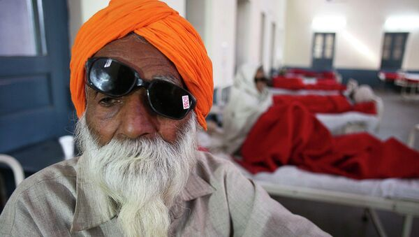 A man sits on a bed while waiting for treatment at a hospital after undergoing cataract removals from a free eye surgery camp, in the northern Indian city of Amritsar - Sputnik International