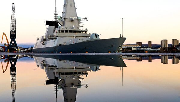 Royal Navy Type 45 destroyer HMS Defender is mirrored in water following a downpour on the dockside - Sputnik International