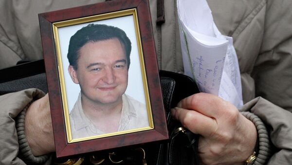 Portrait of lawyer Sergei Magnitsky who died in jail, is held by his mother Nataliya Magnitskaya, as she speaks during an interview with the AP in Moscow - Sputnik International