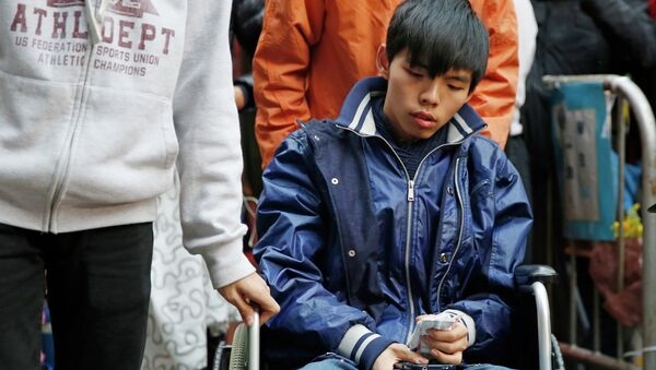 Student leader Joshua Wong attends a news conference as he sits on a wheel chair - Sputnik International