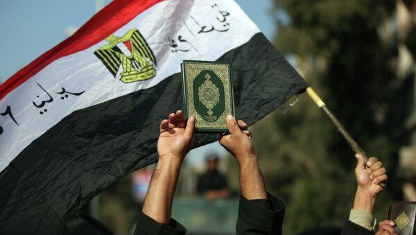 An Egyptian man holds up the a copy of Quran - Sputnik International