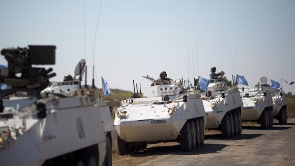 Armored vehicles from the UN peacekeepers of the United Nations Disengagement Observer Force, also known as UNDOF wait to cross from the Israeli controlled Golan Heights to Syria. - Sputnik International