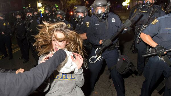 A protester flees as police officers try to disperse a crowd comprised largely of student demonstrators during a protest against police violence in the U.S., in Berkeley, California early December 7, 2014 - Sputnik International