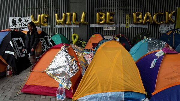 A protester walks past tents outside the government headquarters at Admiralty in Hong Kong December 10, 2014. - Sputnik International