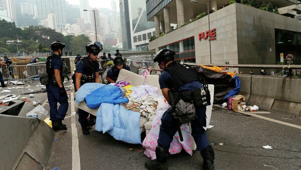 Police remove a sofa as they clear an area previously blocked by pro-democracy protesters near the government headquarters building at the financial Central district in Hong Kong, December 11, 2014 - Sputnik International