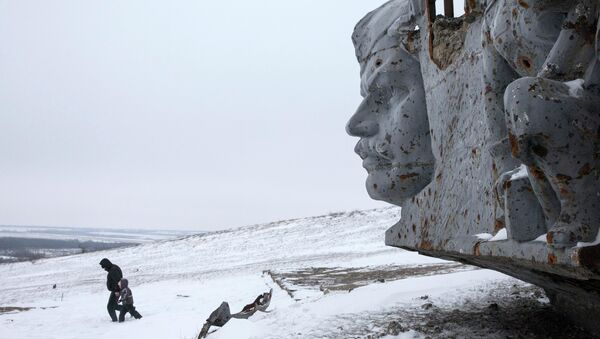 A man and a child walk in the snow at the destroyed war memorial at Savur-Mohyla, a hill east of the city of Donetsk - Sputnik International