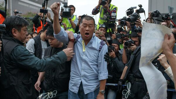 Tycoon and Apple Daily Newspaper owner shouts slogan before he is taken away by police officer at an area previously blocked by pro-democracy supporters, outside the government headquarters in Hong Kong - Sputnik International