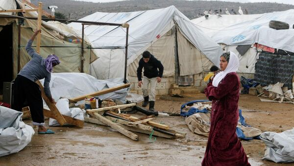 A woman walks past Syrian refugees dismantling their tents at a makeshift settlement in al-Rafid town, in the Bekaa valley - Sputnik International