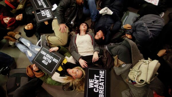 Protesters rallying against a grand jury's decision not to indict the police officer involved in the death of Eric Garner stage a die-in at the Apple Store on Fifth Avenue - Sputnik International