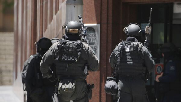 Armed police stand at the ready close to a cafe under siege at Martin Place in the central business district of Sydney, Australia, Monday, Dec. 15, 2014 - Sputnik International
