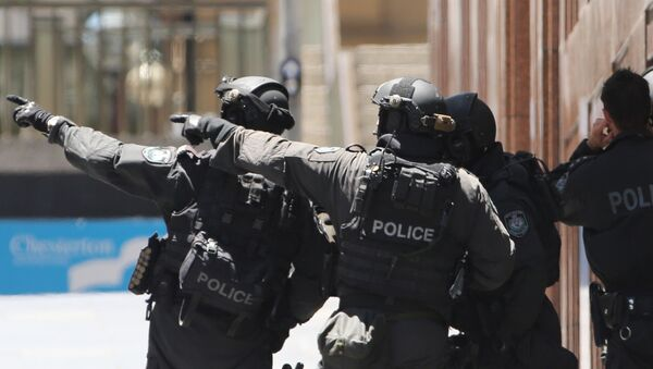 Armed police officers point as they stand at the ready close to a cafe under siege at Martin Place in Sydney, Australia, Monday, Dec. 15, 2014 - Sputnik International