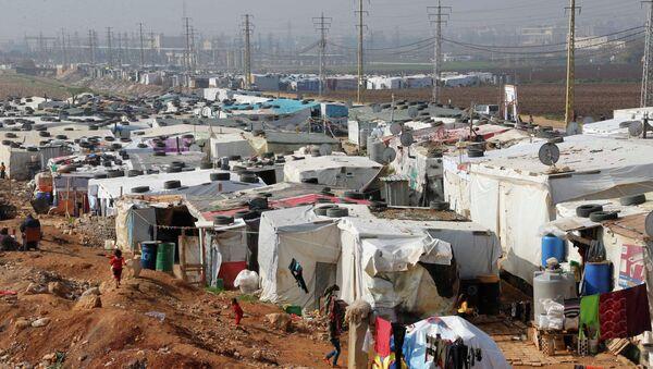 Syrian refugees walk at a refugee camp in Zahle in the Bekaa valley November 18, 2014 - Sputnik International
