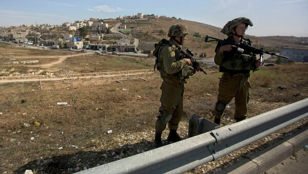 Israeli soldiers stand guard on the main road near the West bank village of Bet Sahour during the funeral of Dalia Lemkus, at the West Bank Jewish settlement of Tekoa, Tuesday, Nov. 11, 2014 - Sputnik International