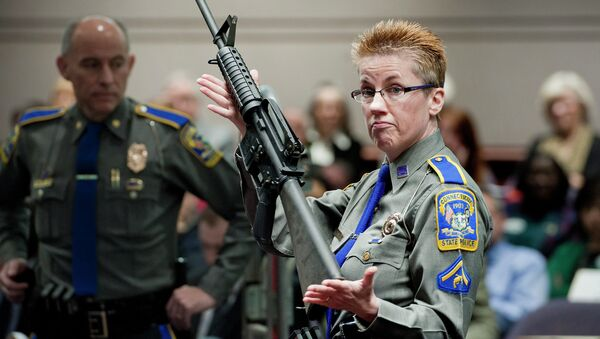 In this Jan. 28, 2013, file photo, firearms training unit Detective Barbara J. Mattson, of the Connecticut State Police, holds up a Bushmaster AR-15 rifle, the same make and model of gun used by Adam Lanza in the Sandy Hook School shooting, for a demonstration during a hearing of a legislative subcommittee reviewing gun laws, at the Legislative Office Building in Hartford, Connecticut. - Sputnik International