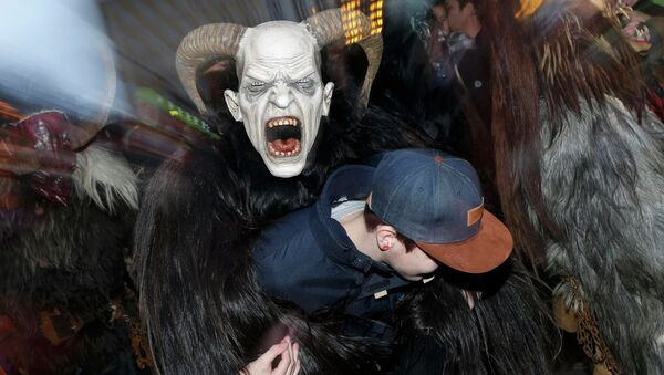 A man dressed as 'Krampus' creature takes part in a parade at Munich's Christmas market - Sputnik International