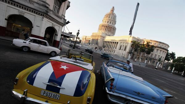 A car with a Cuban flag is parked near Cuban Capitol in Havana December 18, 2014. Cuban President Raul Castro hailed a landmark exchange of prisoners with the United States on Wednesday and praised U.S. President Barack Obama as the two countries agreed to normalize relations after more than five decades of hostility - Sputnik International