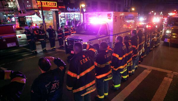 An ambulance carrying one of the two New York Police officers who were shot dead passes by a New York Fire Department honor guard along Broadway in the Brooklyn borough of New York - Sputnik International
