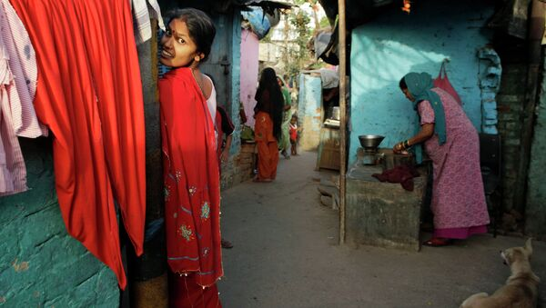 An Indian woman reacts to the camera as another sells meat in a narrow alley at a slum area in New Delhi, India, Tuesday, May 21, 2013 - Sputnik International