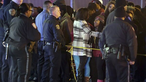 Police hold back a crowd at the perimeter of a scene on Wednesday, Dec. 24, 2014, following a shooting Tuesday at a gas station in Berkeley, Mo. St. Louis County police say a man who pulled a gun and pointed it at an officer has been killed. - Sputnik International