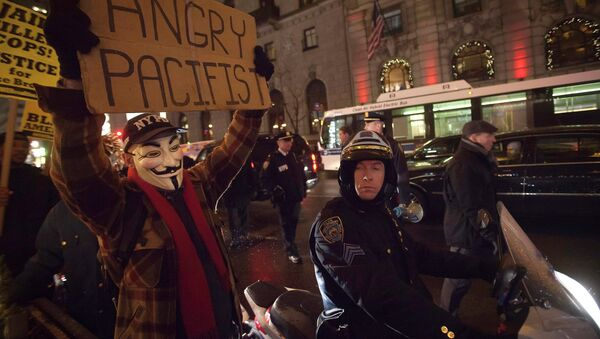 A demonstrator wearing a Guy Fawkes mask walks up 6th Ave as he protests against the police in the Manhattan borough of New York December 23, 2014 - Sputnik International