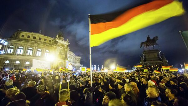 Participants hold German national flags during a demonstration organised by anti-immigration group PEGIDA  outside Semperoper opera house in Dresden December 22, 2014 - Sputnik International