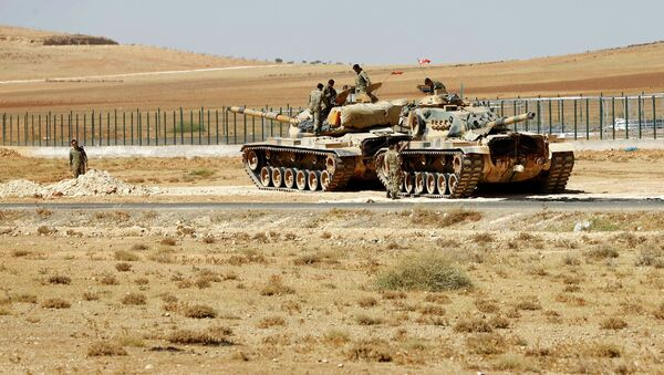 Turkish soldiers stand on top of tanks next to the Syrian-Trukish border fence - Sputnik International