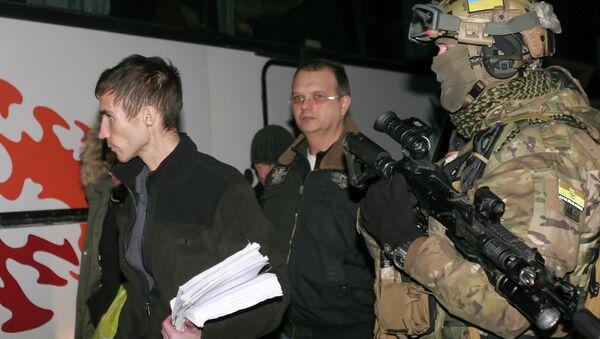 Members of independent supporters walk past a Ukrainian serviceman during an exchange of prisoners of war outside Donetsk - Sputnik International