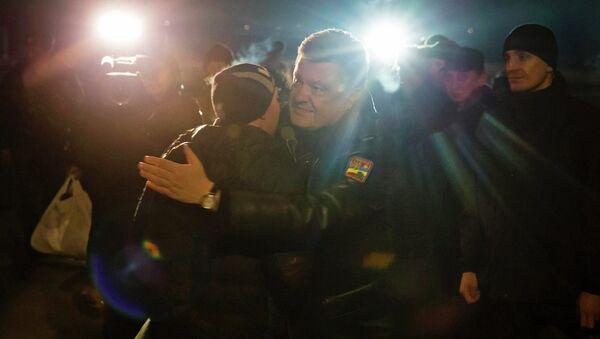 Ukraine's President Petro Poroshenko (C) greets a Ukrainian prisoner-of-war returning home after being exchanged for independence supporters, in Kiev. - Sputnik International