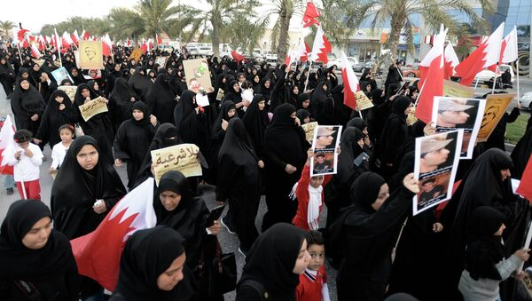 Protesters holding pictures of Al Waad President Ebrahim Shareef march during an anti-government rally organised by Bahrain's main opposition party, Al Wefaq in Budaiya west of Manama, December 26, 2014 - Sputnik International