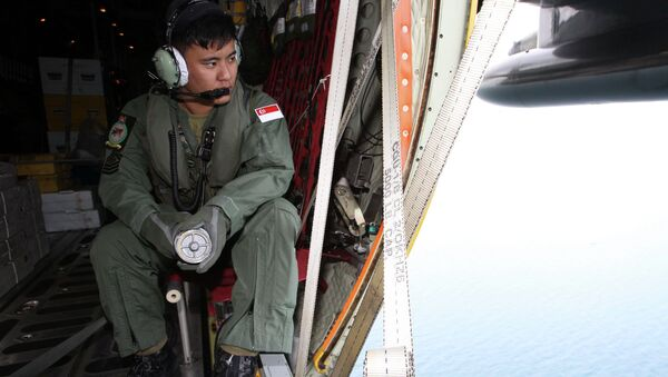A member of the Republic of Singapore Air Force (RSAF) looks out into the waters, onboard a C-130 Hercules, during a Search and Locate operation for the missing AirAsia QZ8501 aircraft over an undisclosed search area December 29, 2014 - Sputnik International