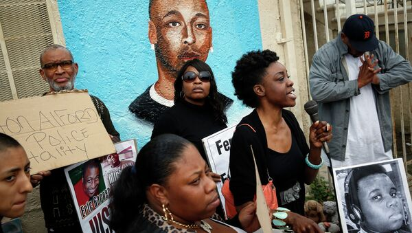 Demonstrators rally against the Missouri grand jury's decision to not indict Darren Wilson for his fatal shooting of Michael Brown, in front of a mural of Ezell Ford - Sputnik International