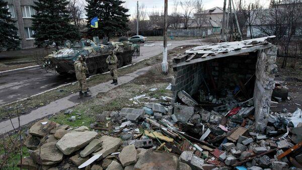 Ukrainian servicemen stand near a building damaged during fighting between militia and Ukrainian government forces in the eastern Ukrainian town of Debaltseve in Donetsk region, December 24, 2014 - Sputnik International