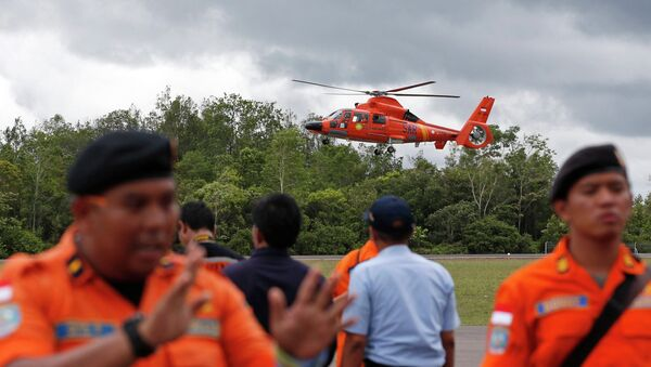An Indonesian Search and Rescue helicopter carrying the bodies of two AirAsia passengers recovered from the sea prepares to land at the airport in Pangkalan Bun, Central Kalimantan, December 31, 2014 - Sputnik International