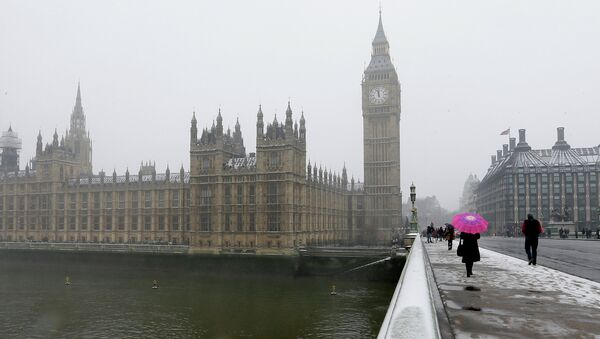 A woman carrying a pink umbrella walks across Westminster Bridge, with the Palace of Westminster in the background as it begins to snow in London, Friday, Jan. 18, 2013 - Sputnik International