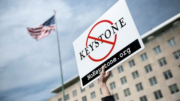 An activist holds up a sign outside the State Department during a protest of the Keystone XL pipeline on March 7, 2014 in Washington - Sputnik International