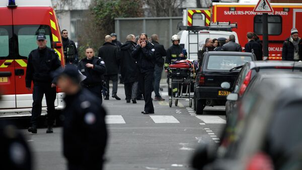 Police officers and firemen gather outside the French satirical newspaper Charlie Hebdo's office, in Paris, Wednesday, Jan. 7, 2015 - Sputnik International