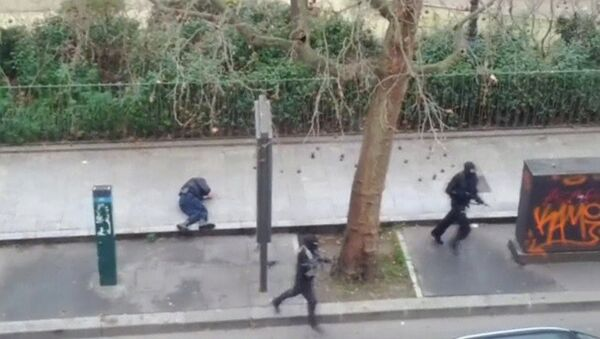 Gunmen flee after shooting a wounded police officer (L) on the ground at point-blank range, outside the offices of French satirical newspaper Charlie Hebdo in Paris - Sputnik International