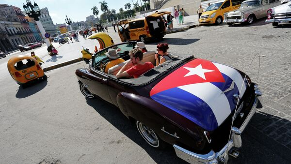 In this Dec. 18, 2014 file photo, tourists take a ride in a classic American convertible car with the Cuban national flag painted on the trunk, in Havana, Cuba - Sputnik International